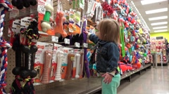 Stock Video Footage of Toddler price shopping dog play toys at big box pet store.