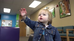 Toddler in jean jacket reaching at pediatrics doctors office waiting room. Stock Footage