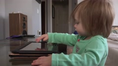 Toddler tablet computer taps and swipes closeup on coffee table. Stock Footage