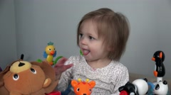 Toddler soothing teething pain with fingers in mouth on toy setup. - stock footage
