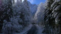 Aerial - Descending above wintry road with a view at the mountains Stock Footage