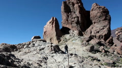 Man walks on Roques Garcia formations with Roque Cinchado famous rock. Teide Stock Footage
