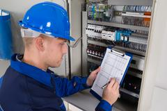 Young Male Technician Holding Clipboard While Examining Fusebox Stock Photos