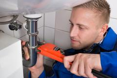 Young Male Plumber Fixing Sink In Kitchen - stock photo