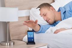 Man Lying On Bed Snoozing Alarm On Mobile Phone Screen Stock Photos