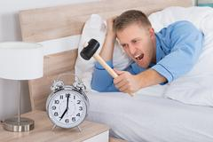 Young Man Smashing Alarm Clock With Hammer On Bed Stock Photos
