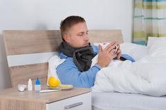 Young Man Suffering From Cold Holding Cup Of Coffee Stock Photos