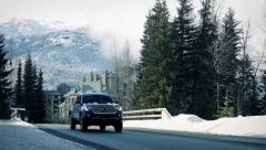 Vehicles Pass In Snowy Mountain Town Stock Footage