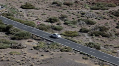 White vehicle driving on asphalt road in mountain valley, aerial view. TF-21 Stock Footage
