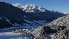 Stock Video Footage of Aerial - Snowy village beneath beautiful sunlit mountain, long shot