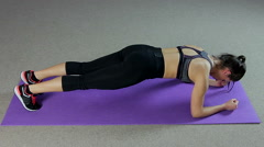 Strong woman doing plank exercise to strengthen muscles and have perfect body Stock Footage