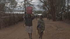 Two African Girls Carrying Water. - stock footage