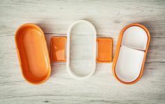 Orange folding plastic food box on the wooden background Stock Photos