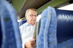 Stock Photo of happy senior man reading newspaper in travel bus