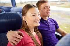Happy teenage couple or passengers in travel bus Stock Photos