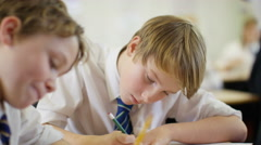 4K Young students working at their desks in school classroom - stock footage