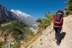 Female hiker ascending a slope. - stock photo