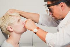 Doctor ENT checking ear with otoscope to woman patient - stock photo