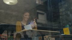 Beautiful, curly hear girl,laughing and redaing a book in caffe - stock footage