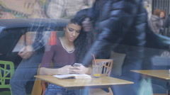 Beautiful brunette, curly hair girl, reading book in caffee Stock Footage