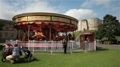 Stock Video Footage of CLIFFORDS TOWER & FAIRGROUND CAROUSEL YORK NORTH YORKSHIRE