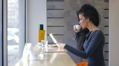 Stock Video Footage of Businesswoman on coffee breake, reading tablet, drinking coffe