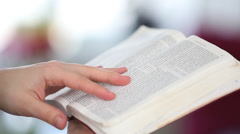 Person reading trough the Bible and turning a page Stock Footage