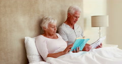 Senior couple sitting in bed reading Stock Footage