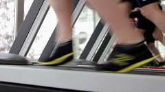 Legs of many people doing exercises on treadmill in sports club, motivation - stock footage