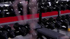Sports equipment for iron pumping, dumbbells on shelves in the gym, atmosphere Stock Footage