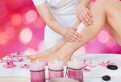 Midsection of beautician waxing woman's leg with wax strip at beauty salon - stock photo