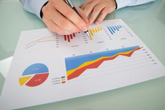 Close-up Of Businessman Analyzing Graphs On Paper - stock photo