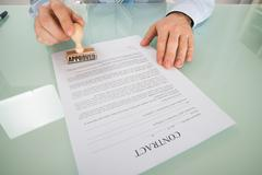 Close-up Of Businessman Stamping To Approve Contract Form Stock Photos