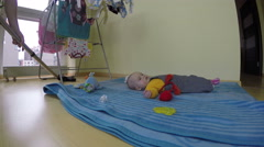 Cleaning up room, child lie on blue mat. Home hoovering. 4K Stock Footage