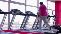 Fat senior woman walking on treadmill in the gym, active workout for weight loss Stock Footage