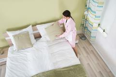Young Female Housekeeper Arranging Bedsheet On Bed In Room Stock Photos