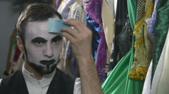 Handsome young man applying white face painting for mime make-up - stock footage