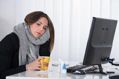 Young Businesswoman With Cup Of Hot Beverage Sitting At Desk Stock Photos