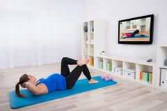 Young Pregnant Female Doing Workout In Front Of Television - stock photo