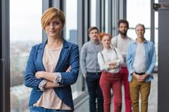 Stock Photo of Corporate portrait of young business woman with her colleagues in background.