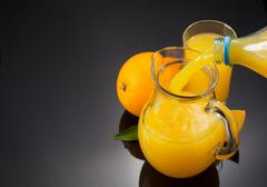 glass pitcher and orange juice on black - stock photo