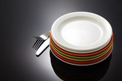 plate and fork with knife on black - stock photo