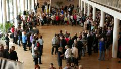 People crowd around empty space in front of stage, concert hall lobby room Stock Footage