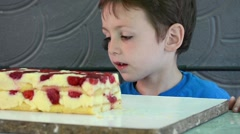 Boy who steals a cream cake with crackers and berries that is not yet ready - stock footage