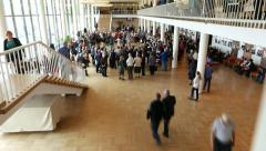 People crowd in concert hall lobby room, round in circle, some dance in middle Stock Footage