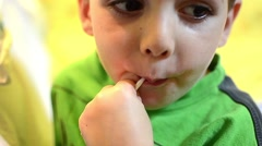 Boy dressed in a green shirt, eat a candy lolly orange and is very happy Stock Footage