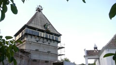 Worker descends a bucket with a pulley from the roof of an old fortress tower Stock Footage