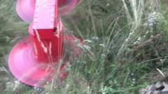 Tractor mowing sea grass grown on land behind the house. After it dries it will Stock Footage
