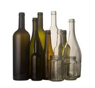 Horizontal front view of a group of glass bottles and jars in different colors i Stock Photos