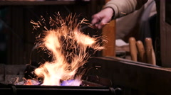 Man preparing the fire for roasting the food at the Christmas market in Budapest Stock Footage